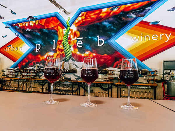 pleb urban winery with 3 glasses of red wine and their urban art mural and logo