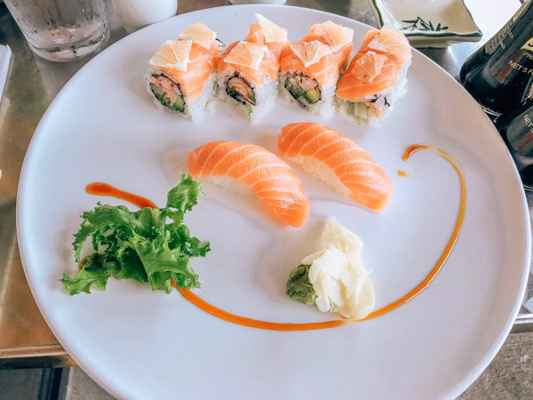 Zen Sushi Asheville NC with large white plate, two salmon sashimi, and a sushi roll topped with raw salmon and lemon wedges.