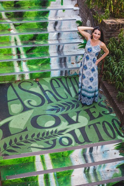 """Downtown Asheville Street Art with brunette woman in a dress standing on the stairs with the saying """"Asheville loves you too."""""""