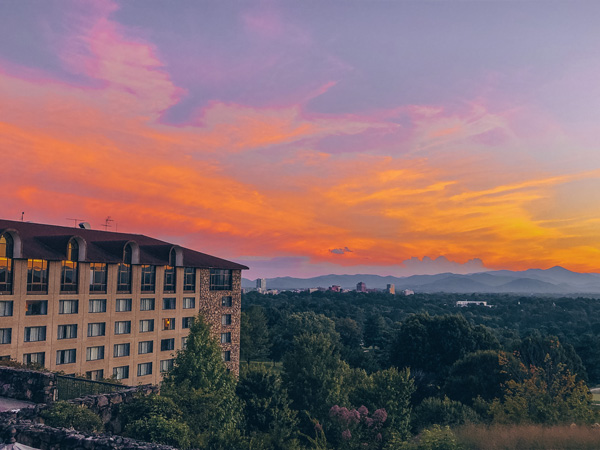 Pros of Living In Asheville NC Grove Park Sunset with purple, pink and orange sky over downtown Asheville, North Carolina