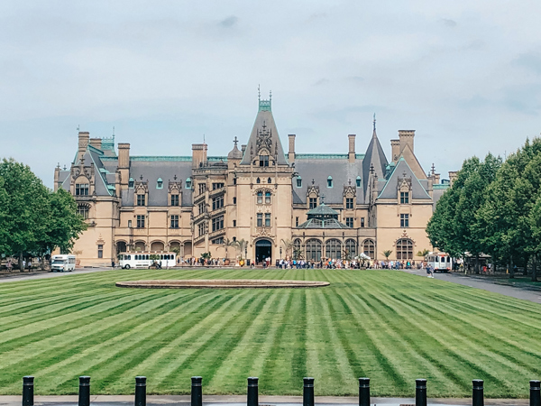 Biltmore Estate Asheville NC house with green grass and people and shuttles out front