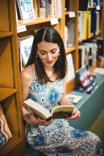 Malaprop's Bookstore Asheville white brunette woman sitting on the corner surrounded by bookshelves and reading Thomas Wolfe's Look Homeward, Angel