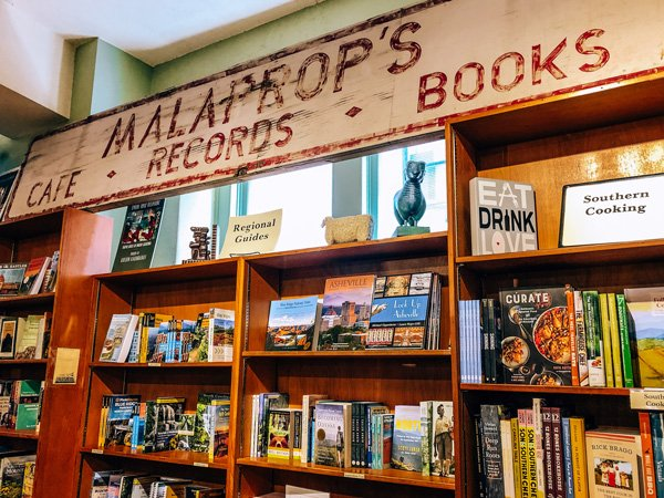 Malaprop's Bookstore/Cafe Asheville, NC picture with Malaprop's sign over wooden bookshelves filled with books