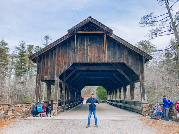 Asheville Waterfall Hikes Covered Bridge (wooden) at High Falls in DuPont Forest with white male hiking standing in front with hat and backpack