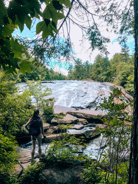 Asheville Waterfalls Bridal Veil Falls DuPont State Recreational Forest waterfalls with brunette white woman wearing a hiking backpack and looking at the waterfalls