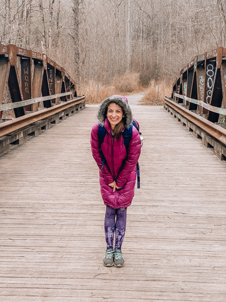 Daniel Ridge Loop and Falls with white brunette woman crossing a bridge wearing a plum coat