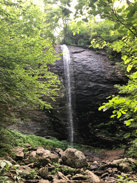 Douglas Falls Pisgah National Forest tall waterfall coming over a large rock onto smaller rocks