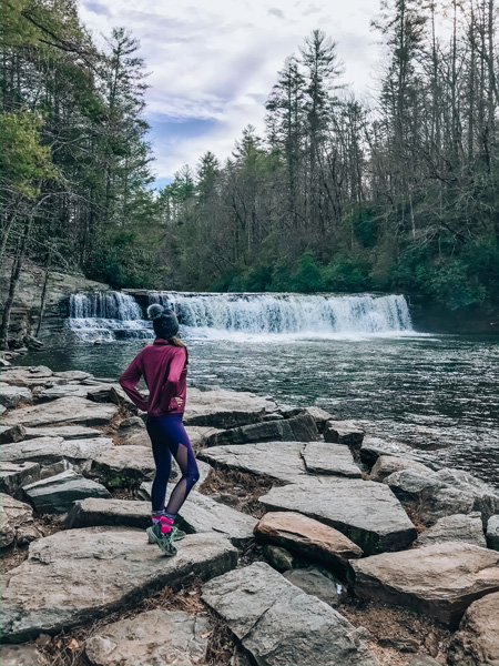 Hooker Falls at DuPont State Recreational Forest brunette white woman in pink and purple hiking gear in front of a waterfall near Asheville NC
