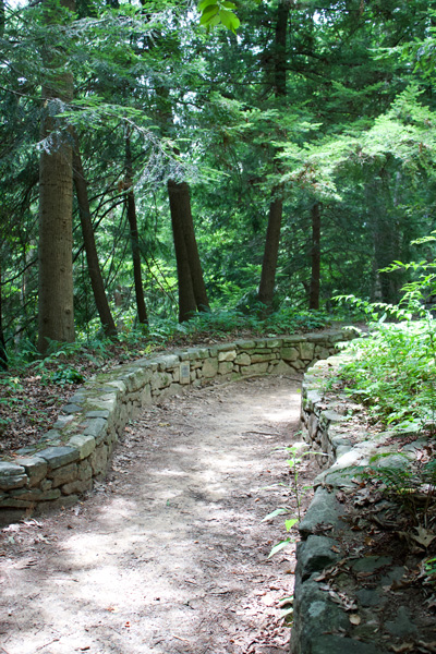 Dirt trail with stone wall at the Botanical Gardens at Asheville