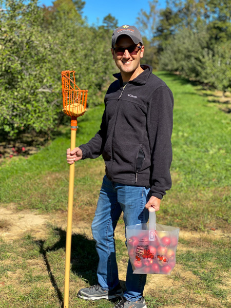 Coston Farm Apple Picking Hendersonville NC with white male in black fleece holding bag full of U-Pick apples and apple picker in apple orchards