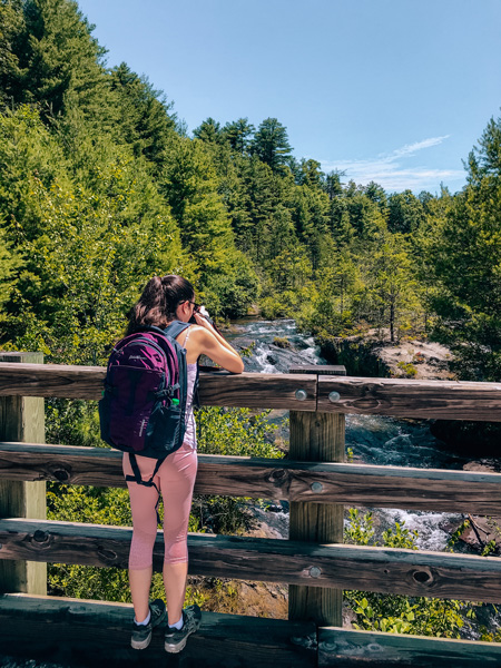 Lake Julia Spillway at DuPont State Recreational Forest with white brunette woman in pink yoga pants and a hiking backpack taking a picture of the mini waterfalls