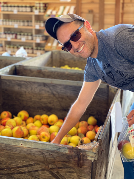 Stepp's Hillcrest Apple Orchard Hendersonville NC with white male in blue shirt with sunglasses and hat reaching into bin of pre-picked apples in farm store