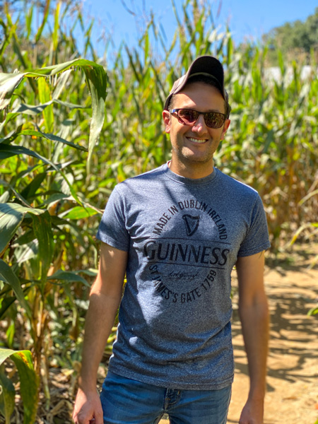 Stepp's Hillcrest Orchard Corn Maze with white male in blue shirt and sunglasses surrounded by tall corn stalks