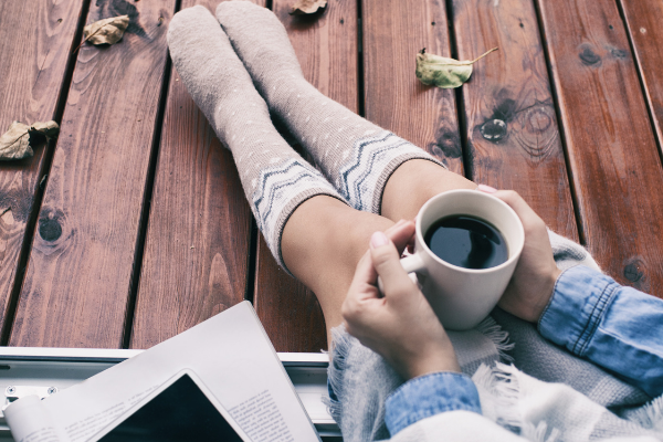 Asheville NC fall reading with white woman wearing long knee-high beige socks, drinking a hot cup of coffee, and sitting next to a pile of books