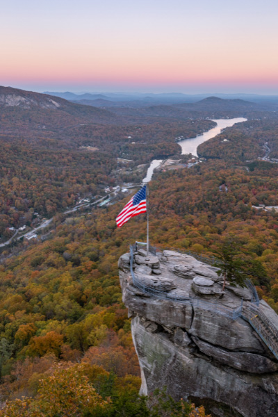 Chimney Rock North Carolina Fall with rock jutting out with American flag and view of Lake Lure