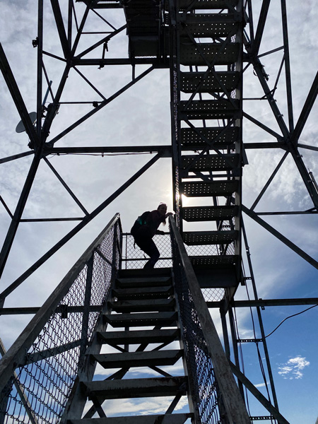 Fryingpan Lookout Tower steel stairs with a woman wearing a hiking backpack going up them