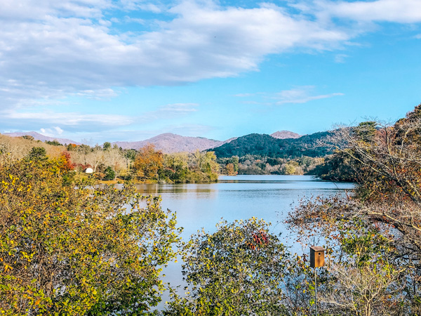 Parks In Asheville NC Beaver Lake with blue lake surrounded by Blue Ridge Mountains and fall foliage trees