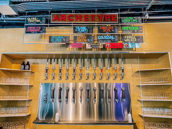 Archetype Brewing West Asheville with picture of beer taps surrounded by shelves of clean glasses on either side