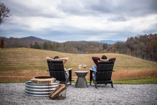 Asheville Fall Things To Do Marked Tree Vineyards with white brunette man and woman sitting in chairs with arms behind head and glasses of wine overlooking the vineyards