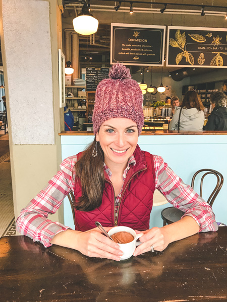 Best Things To Do In Asheville French Broad Chocolate Lounge with brunette white female wearing a red hat and vest with a cup of vegan hot chocolate