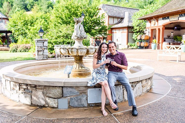 Biltmore Winery in Asheville with white brunette male and woman drinking Biltmore wine sitting in front of a fountain