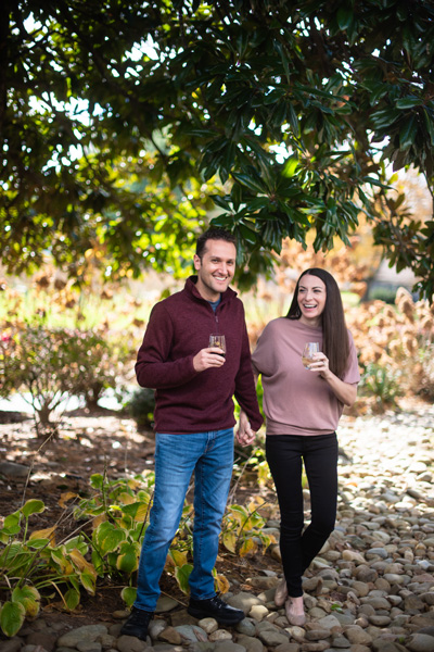 Burntshirt Vineyards Hendersonville NC with white brunette male and female drinking wine and walking.  He is wearing a maroon sweater and she is in a pink top with black pants.