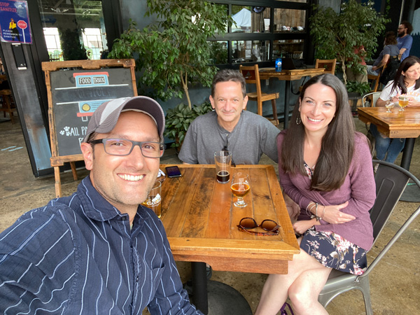Catawba Brewing Co. Downtown Asheville NC with two white brunette men and one female drinking beer at table