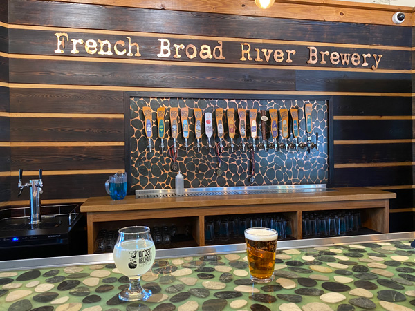 French Broad River Brewery with taps and glass of cider and amber beer