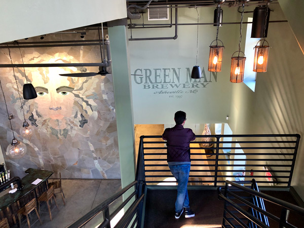 Green Man Brewing In Asheville NC with mural of green man logo and white brunette male looking over railing