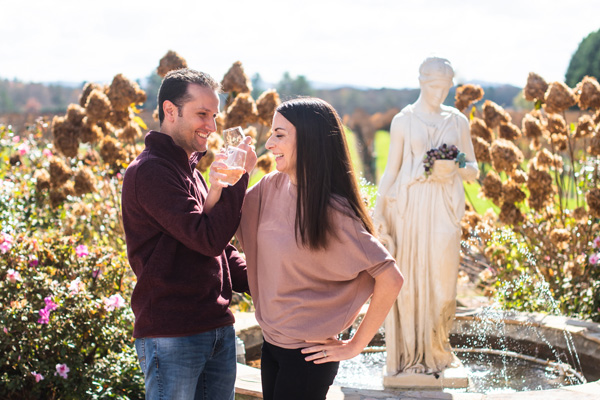 Hendersonville Wineries Burntshirt Vineyards with brunette white male and female drinking wine in front of a white statue and fountain