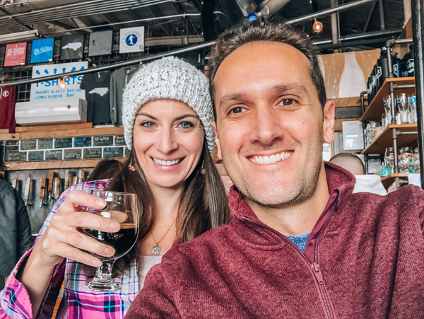Hi Wire Brewing South Slope Asheville NC with brunette white male and female taking a selfie and holding beer