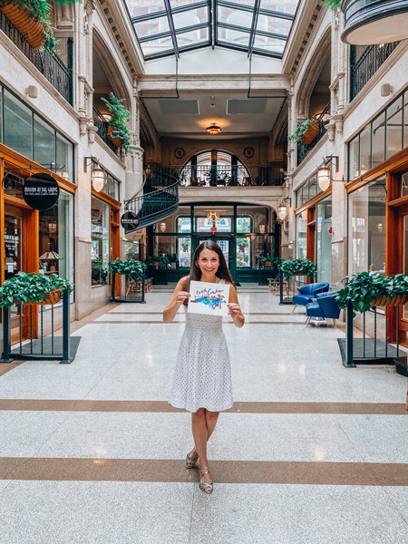 Historic Grove Arcade Asheville North Carolina with white brunette female holding a map of NC
