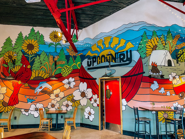 UpCountry Brewing Asheville NC with colorful wall mural with sun, blue mountains and flowers