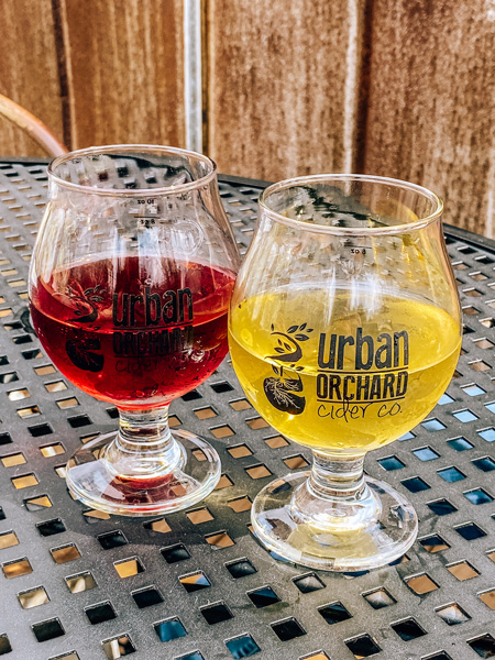 Urban Orchard Cider Co. West AVL with red and yellow cider on a patio table