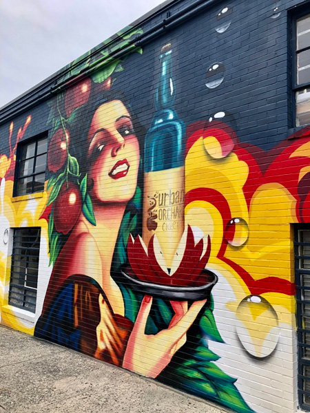 Urban Orchard Cider Company from of the building mural with woman holding bottle of wine on a plate