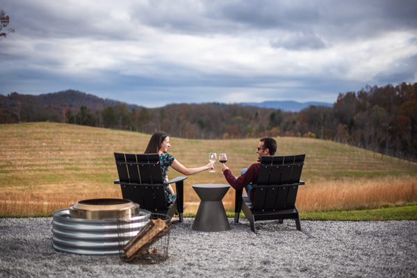 Wineries In and Near Asheville Marked Tree Vineyard with brunette white male and female sitting in chairs looking out at the mountains doing a cheers with glasses of wine