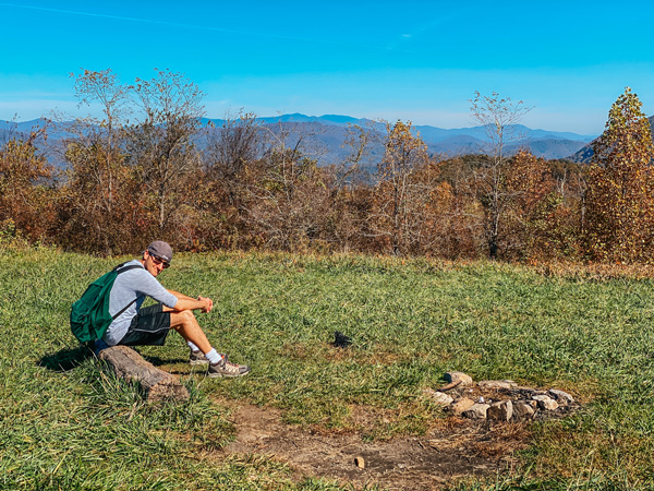 Picnic Spot At Trombatore Trail Blue Ridge Pastures with brunette white male wearing a green hiking backpack sitting on a logPicnic Spot At Trombatore Trail Blue Ridge Pastures