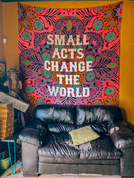 Adam Dalton Distillery Asheville NC with leather couch and tapestry that says Small acts change the world