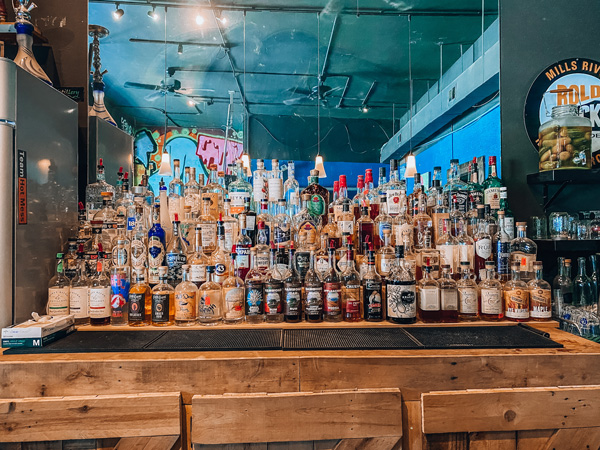 Adam Dalton Distillery Bar Asheville with alcohol lined up and mirror