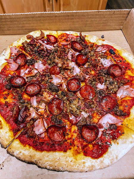 Asheville Brewing Pizza Delivery Takeout with meat lovers pizza with ham, pepperoni and red sauce