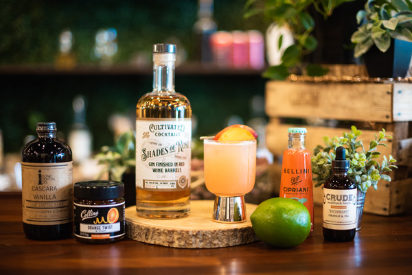 Asheville Distilleries Cultivated Cocktails with peach cocktail, SHodes of Rose gin, bitters, vanilla, and Bellini mix