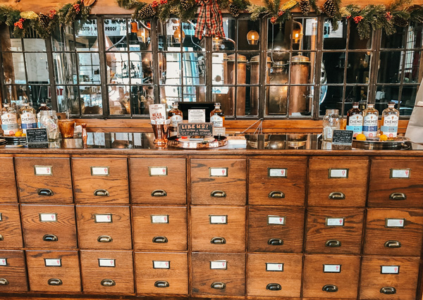 Chemist Spirits Distillery Asheville with wooden bar that looks like file holders and distillery in background