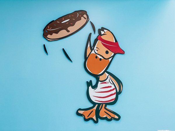 Duck Donuts Asheville NC with blue wall and duck wear red visor flipping a chocolate glazed donut
