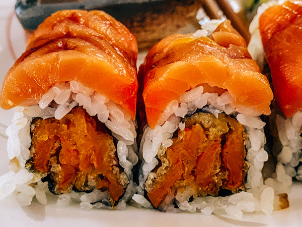 Hana Japanese Hibachi Sushi Bar Restaurant Asheville with sweet potato tempura sushi roll topped with smoked salmon and eel sauce