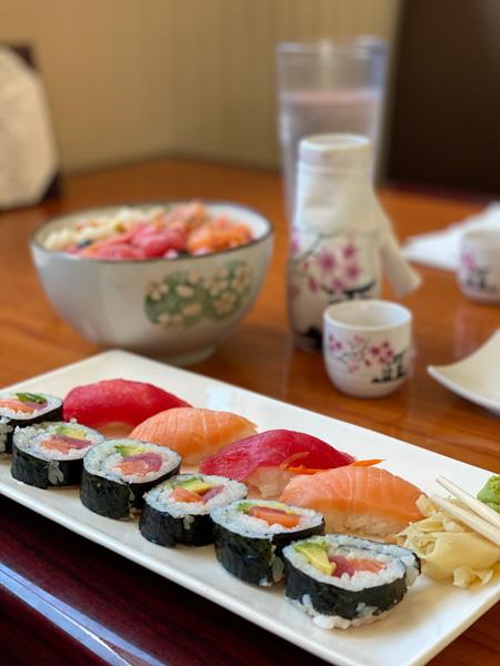 Mr. Sushi Asheville with Sushi Rolls, Sashimi, sake glasses, and Poke salad
