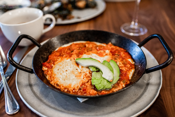Takeout in Asheville NC Tupelo Honey Southern Shakshuka in a black skillet with avocado