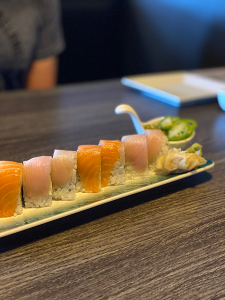 The Madness Asheville Sushi Roll with tuna and salmon alternating on top