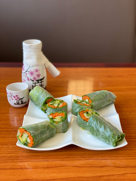 Veggie Summer Rolls with sake at Mr Sushi Asheville. Rolls are filled with avocado, cucumber, and carrots and wrapped in rice paper with sake behind the plate