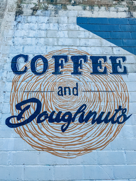 Vortex Doughnuts Asheville with blue and gold-ish brown coffee and doughnuts mural on side of building