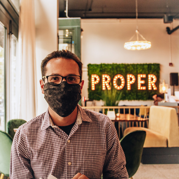 Asheville Proper Steak restaurant with white brunette male wearing a mask